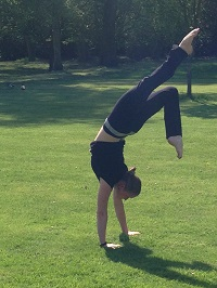 Sasha doing a handstand on the lawn at St Katharine's yoga retreat